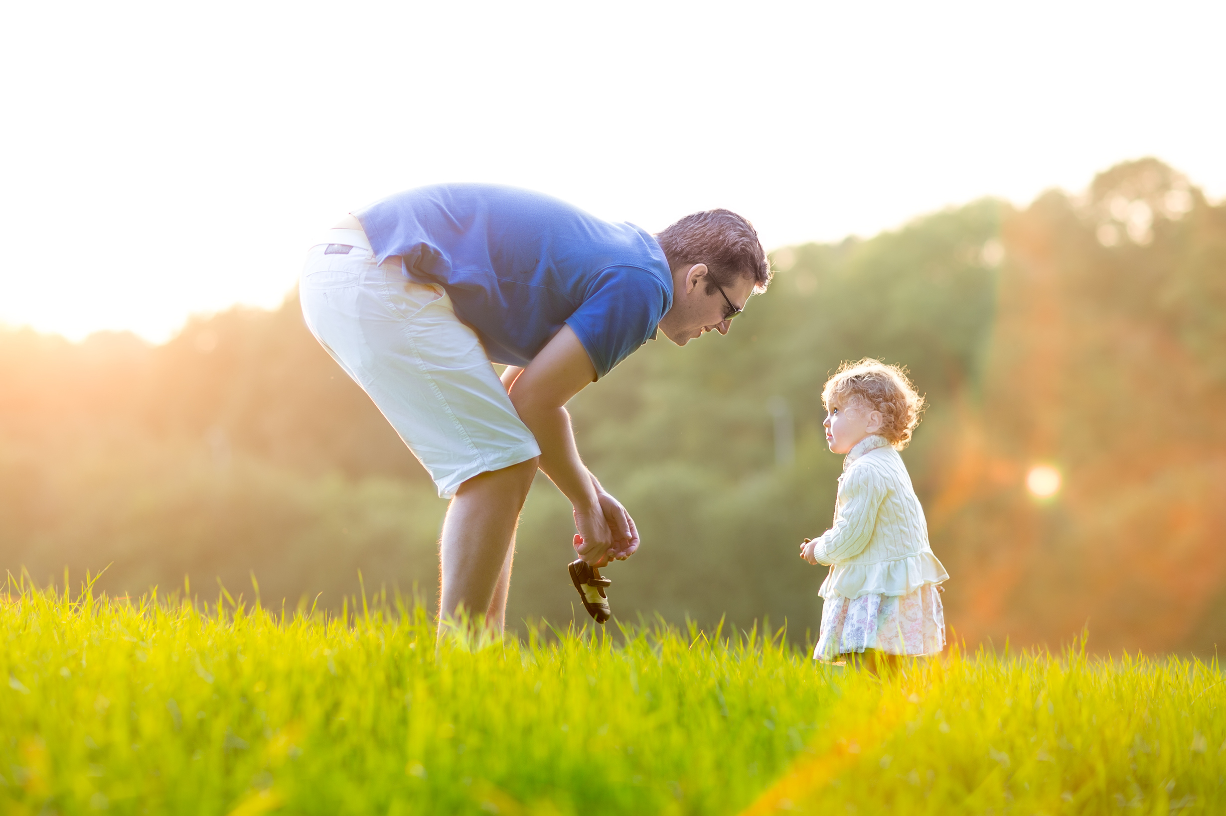 Young father playing with his baby daughter in a field on a sunny autumn evening