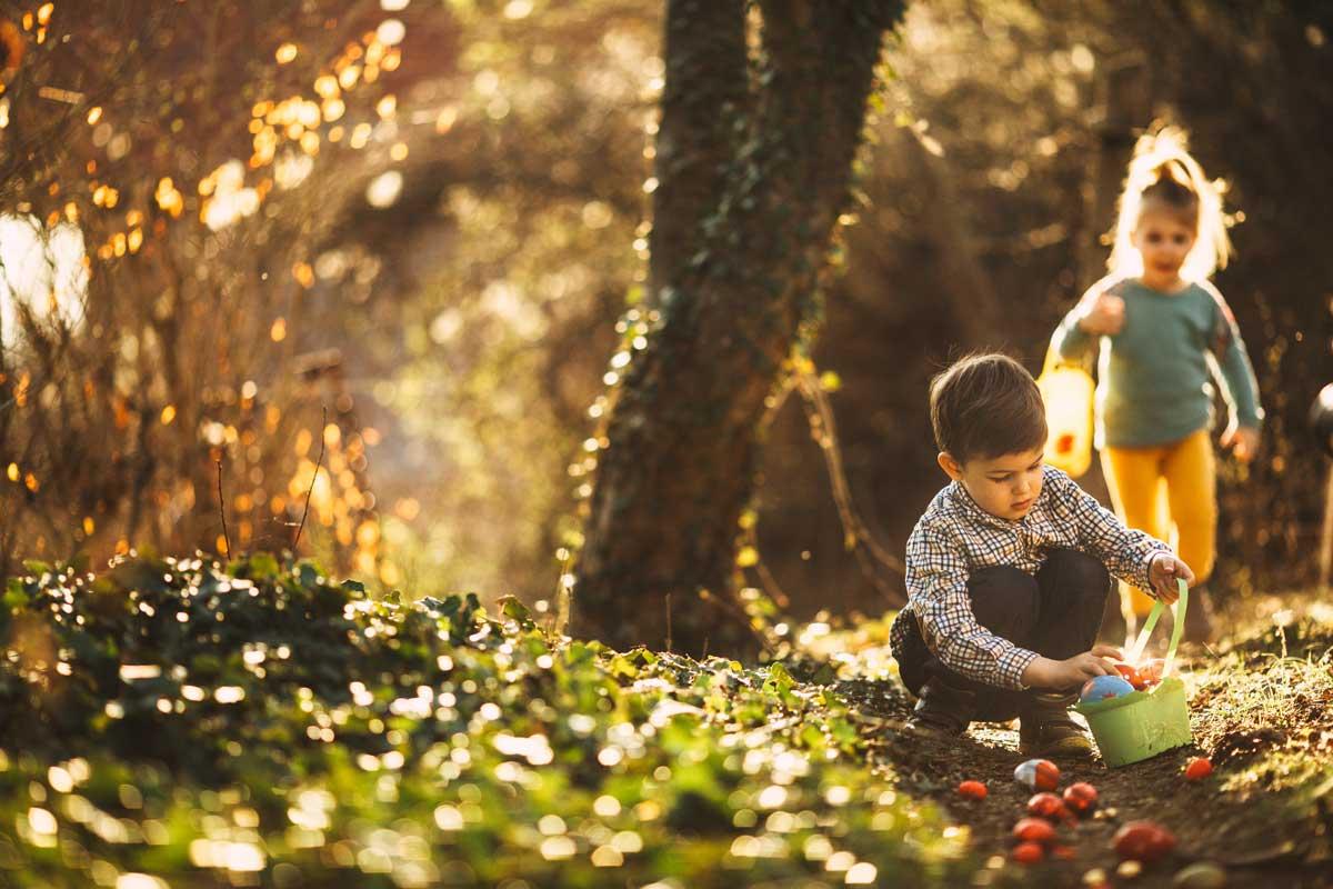 Kinder suchen am Karsamstag bunte Ostereier im Garten.